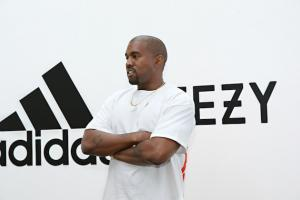Kanye West in white with arms folded, in front of white wall with black text
