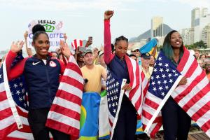 Kristi Castlin, Brianna Rollins and Nia Ali wrapped in red, white and blue American flags with blue sky and brown beach in the background