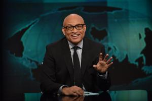 Larry Wilmore in black suit with black tie and striped shirt against green-blue background