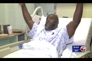 Black man in a white hospital gown sits in a bed with his hands above his head