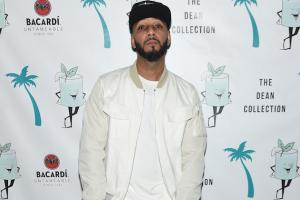 Swizz Beatz in black hat and white outfit against white and blue background