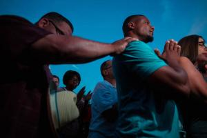 Two middle Black men mourn at protest against the police killing of Sylville Smith