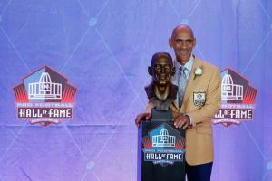 Tony Dungy in beige suit next to brown metal bust of his head