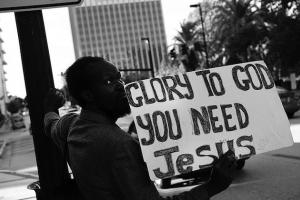 "Black man holds sign that reads: ""Glory to God, you need Jesus."""