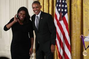 Audra McDonald smiles in black dress next to President Barack Obama in black suit with grey tie