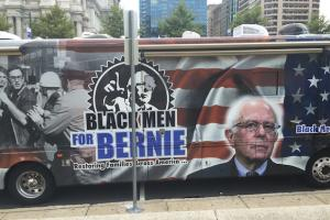 "Bus reading ""Black Men for Bernie"" in black and blue text under black-and-white image of Bernie Sanders, all set against red, white and blue American flag background"