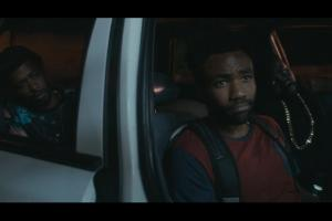 Three black men in grey car, one with red and blue shirt and black backpack and another with black shirt and gold chain