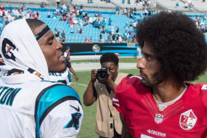 Cam Newton in white jersey with black and blue lettering next to Colin Kaepernick in red jersey with white lettering
