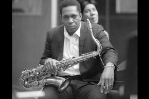 Black-and-white image of John Coltrane, seated in a suit and white shirt with saxophone