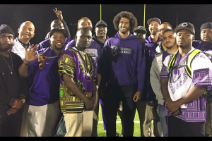 Black man surrounded by young black men in purple gear against yellow goal post and green field with black sky