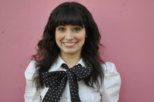 Smiling woman in white shirt with black bow with white polka dots against pink background