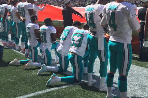 Dolphins players in light blue/green and white jerseys, four kneeling on one knee