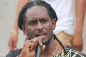 Black man with black dreadlocks wearing black t-shirt and holding black and grey microphone