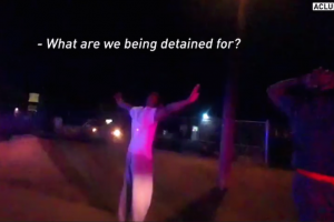 Black man in white shirt stands with hands up, red and blue police lights shining on him