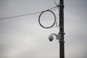 Surveillance camera on a light pole against a gray sky