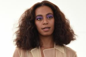 Solange Knowles in beige shirt and purple eyeshadow against white background