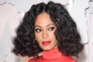 Solange in red turtleneck against white background