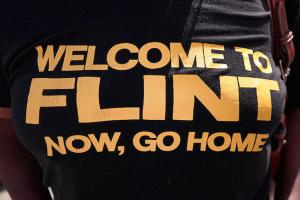 "Black woman wears black shirt with yellow lettering that says: ""Welcome to Flint, now go home."""