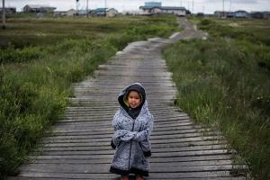 A Yup'ik child stands on raised, wooden sidewalks, used to help cross unstable ground, on June 30, 2015, in Newtok, Alaska, a village roughly 1500 miles away from where this study took place that is facing relocation due to climate change.