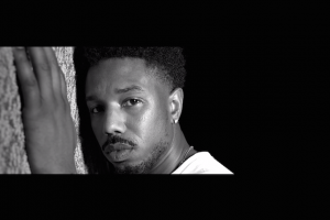 Black and white shot of Michael B. Jordan's face pressed against a wall
