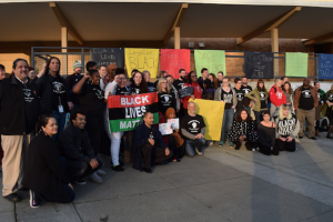 group of people in black clothing standing with multi-colored signs against brown building