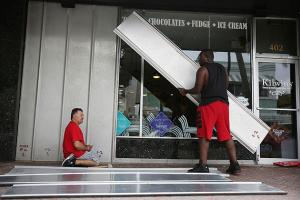 Jason Brock (L) and Kevin Hunter put up hurricane shutters in front of a business as Hurricane Matthew approaches the area on October 6, 2016, in Delray Beach, Florida.