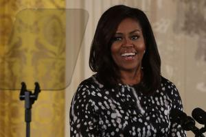 Michelle Obama smiles at podium, wearing black and white dress