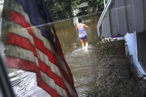 Wanda Sittig walks through the flood waters around her father's home as she helps salvage what she can on August 19, 2016, in St. Amant, Louisiana.