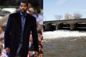 Black man in blue dress shirt and navy blazer with grey dress pants; brown river with brown bridge against blue sky