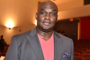 Tommy Ford in grey suit with pink shirt against brown background