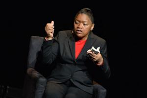 Black woman in black blazer and red shirt holds white packet against black background