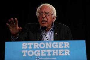 "Bernie Sanders stands behind a podium with ""Stronger Together"" sign"