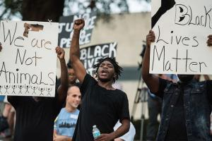 "Young Black men hold up signs that read ""We are not animals"" and ""Black lives matter."""