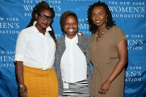 Three Black women stand in front of blue backdrop