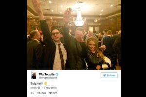 White men in black suits next to Asian woman in black dress, all holding right hands in Nazi salute against brown restaurant background