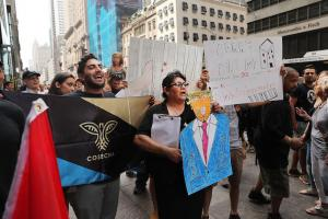 "People holding black blue and gold ""Cosecha"" sign and other signs and blue Donald Trump drawing while wearing Black shirts in front of crowd against grey and black Manhattan skyscrapers"