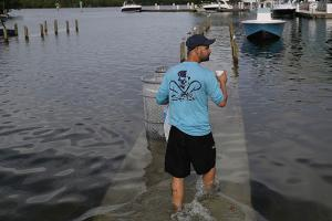 Fernando Sanudo walks along a flooded dock to his boat at the Haulover Marine Center on November 14, 2016, in North Miami, Florida. The flood waters are caused by the combination of the lunar orbit, which causes king tides, and climate change.
