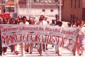 Black and white activists assembled behind white sign with red lettering