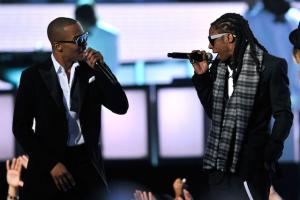 Two Black men face each other, wearing black tuxedos with white shirts and black sunglasses while holding black microphones against blurry purple background