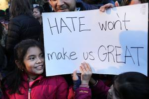 """Girl holds sign that says, """"Hate won't make us great."""""""