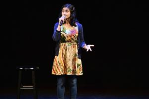 Brown woman in blue cardigan, multicolored dress and black jeans near black stool against black background