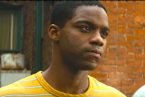 Black man in yellow t-shirt against red brick background