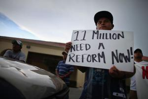 "Man holds sign: ""11 million need a reform now!"""