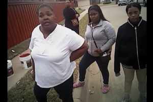 Black woman in white t-shirt and black pants next to Black girl in grey sweatshirt and black pants next to Black girl in black sweatshirt and khaki pants with Black woman with black shirt and brown purse in background, all against brown fence
