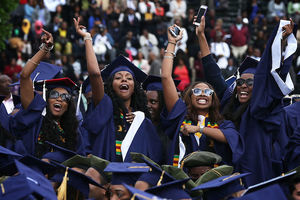 Four Black women in navy commencement robes and caps raise hands behind crowd of navy caps