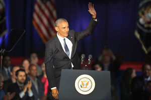Black man in black suit waves at crowd from behind podium.