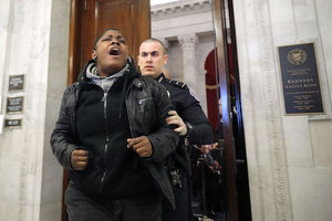 A Black woman protester wearing a black coat is pushed out of a Senate office building by a White policeman