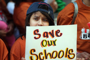 "Girl holds sign that reads, ""Save our schools."""