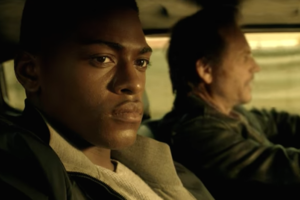 Black man in black hoodie next to White man driving car in green-brown flannel against brown background