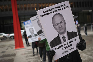 "Protestor holds sign that says, ""Andrew Puzder earns more in one day, than we do in one year. #FightFor15."""